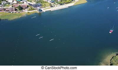 Rowers Training Aerial. People paddle among islands on a lake. Sparkling blue Water on a Sunny Day. Aerial view of Rowers Training on a lake near Trakai castle in Lithuania.
