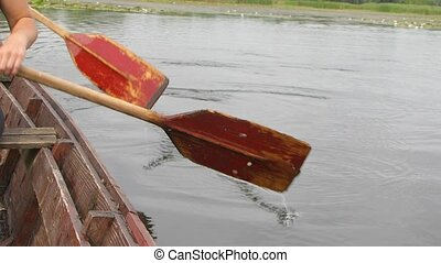 Rowing a boat - Rowing on old wooden boat in a river