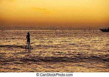 Rowing at the sea at sunset 2