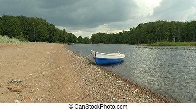 Rowing boat at rope mooring - Rowing boat with oars at rope...