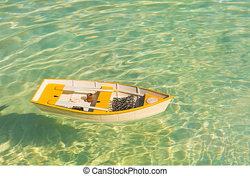 Rowing boat floating on water - Yellow rowing boat floating ...