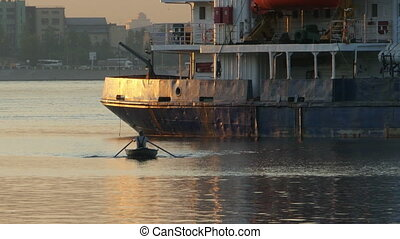 Rowing boat goes on oars next to a large ship