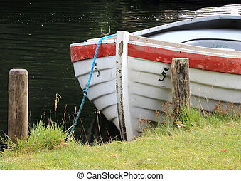 Rowing boat in water at grass field