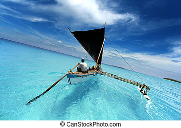 rowing boat sailing in a tropical lagoon