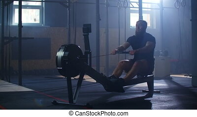 Rowing in the gym. Young man training using rowing machine. slow motion.