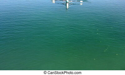 Rowing in the lake - A young man in a boat, paddles on the...