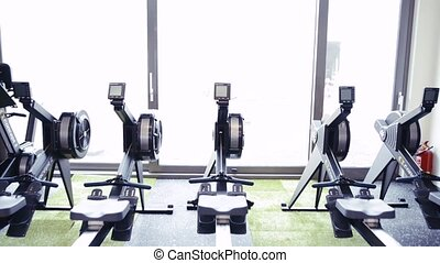 Rowing machines in a row in modern gym - Rowing machines in...