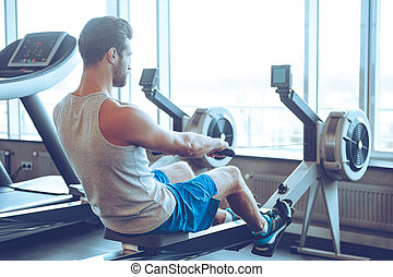 Rowing to success. Side view of young man in sportswear doing rowing in front of window at gym