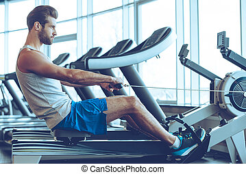 Rowing with power. Side view of young man in sportswear doing rowing in front of window at gym