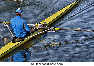 young athlete man rows a boat on the water