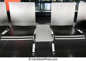 Rows of black chairs at waiting lounge in Airport