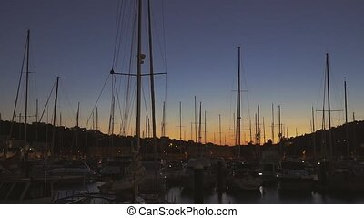 rows of boats at pier in the evening against sunset skies