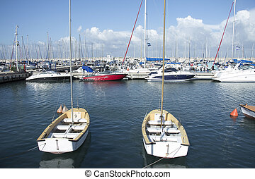 rows of boats in port with cloudy sky