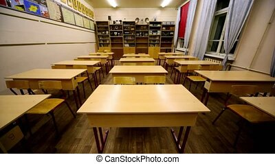 Rows of chairs and tables inside empty physics school class,...