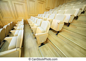 Rows of comfortable beige folding chairs inside big light hall