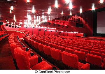 Rows of comfortable red chairs in illuminate red room cinema