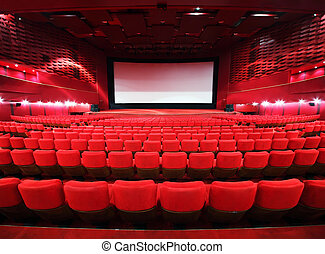 Rows of comfortable red chairs towards to big screen in...