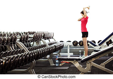 Rows of dumbbells in the gym. Blurred fitness background -...