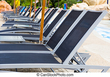 rows of empty modern style beach pool recliner chairs