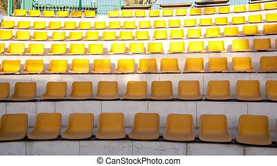 Panning shot of rows of empty yellow seats in the amphitheater