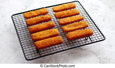 Rows of golden fried fresh fish fingers fillets placed on...