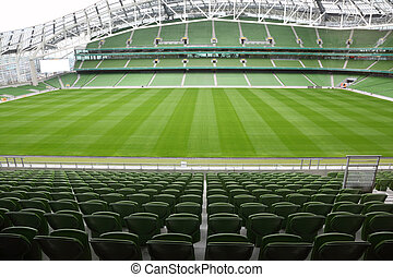Rows of green seats in an empty stadium. Focus on front...