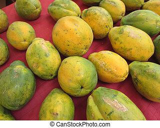 Rows of Hawaiian big rip papayas on red cloth
