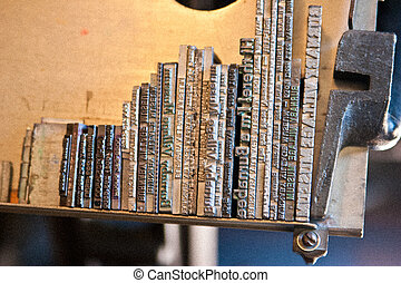 Rows of letters and words that form sentences made from lead metal that were used by an old printing press