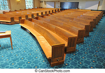Pews in a synagogue facing the stage area with a table in front