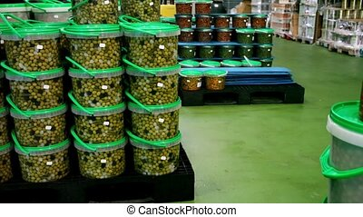 Pickled olives in plastic containers at store warehouse