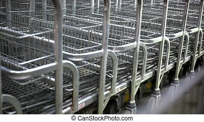 Rows of shopping carts on car park near entrance Of supermarket. Video in shift motion. Macro