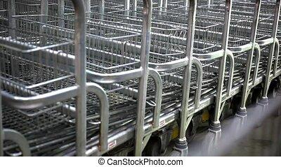 Rows of shopping carts on car park near entrance Of...