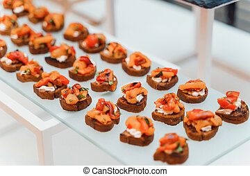 Rows of small delicious canapes on a tray