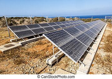 Rows of solar panels on the Sunny sea coast on a hot summer...