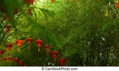 Rows of traditional chinese style red lanterns hanging on bamboo tree tunnel arch.