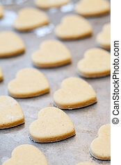 Rows of unbaked heart shaped shortbread cookies on baking tray, selective focus