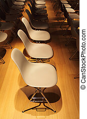 rows of white plastic chairs with chromium-plated legs on...
