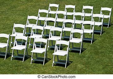 Rows of white wedding chairs horizontal