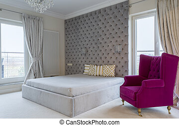 Royal bedroom interior with a purple armchair