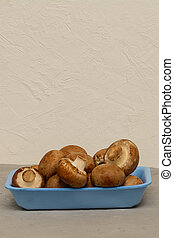 Royal champagnes with brown hat. Mushrooms in blue container for sale store. Copy space, place for text