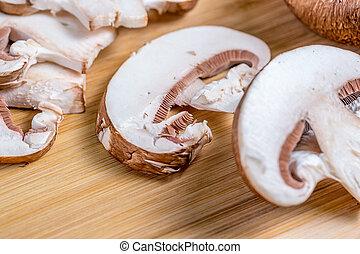 Royal champignons, chopped mushrooms on wooden board close-up