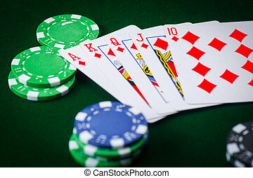 Royal flash and poker chips on green casino table. gambling success