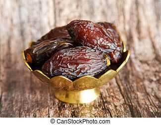 Royal large dates Medjool  in a golden bowl on a wooden background