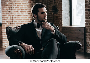 Royalty in his blood. Thoughtful young handsome man in formalwear and bow tie looking away and holding hand on chin while sitting in a chair in loft interior