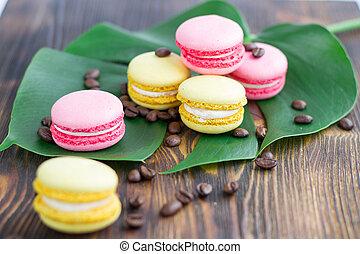 roze, gele, macaroons, koffie bonen, op, groen blad, hout