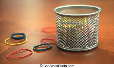 Multi-colored rubber bands being tossed into bin