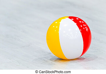 rubber beach yellow white red ball lay on the gray wood floor.