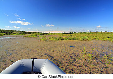 rubber boat on green marsh