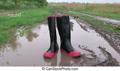 Rubber boots in puddle on a muddy country road after rain