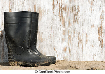 rubber boots on the beach - wheathered wood on beach and a ...